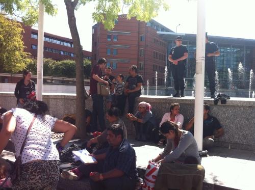 Les Roms évacués, assis devant le parvis de la mairie d'Evry