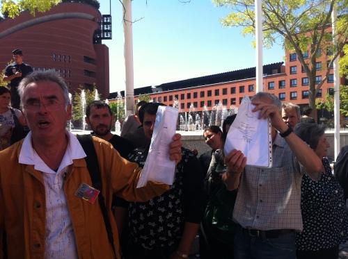Serge Guichard (à gauche) brandissant les certificats de scolarité des enfants Roms
