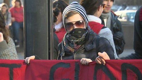 Un manifestant tenant avec ses pairs une bannière sur laquelle on peut lire : « La crise est globale, la lutte est mondiale, résistance générale. »