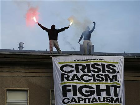 Demonstrators burn flares on the roof of a building above a huge placard during May Day protests in Berlin