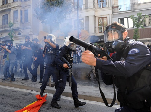 A masked policeman fires teargas during clashes in Istanbul