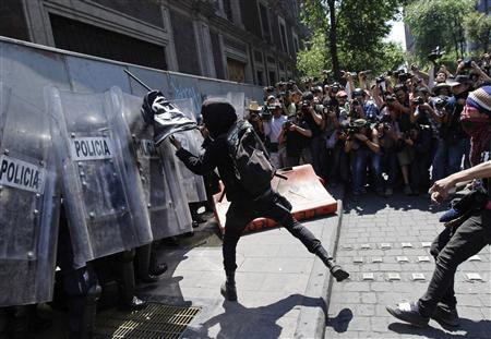 Photographers take pictures as a May Day protester hits the shields of riot police in Mexico City