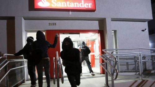 Demonstrators of the group called Black Bloc attack a Santander bank branch during a protest against Sao Paulo State Governor Geraldo Alckmin, in Sao Paulo