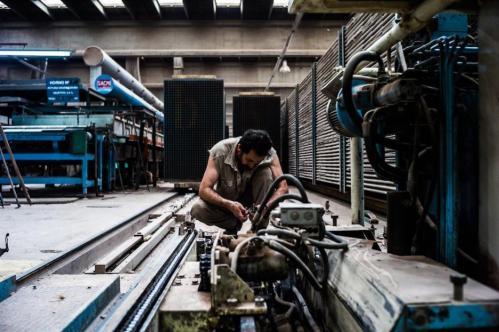 04 Janvier 2013, Neuquén, Argentine. Un ouvrier procède à l'entretien d'une des machines de l'usine. Ces dernières sont pour la plupart trop vieilles pour que l'usine reste compétitive. Des millions de pesos sont nécessaires pour la moderniser, mais ni les banques, ni l'État n'acceptent d'aider.