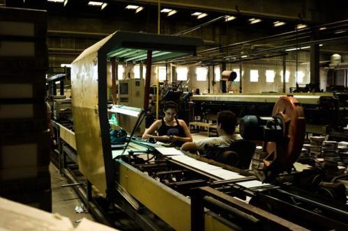 11 Janvier 2013, Neuquén, Argentine. Deux ouvriers discutent à leur poste de travail en triant les plaques de céramiques.