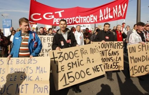 CGT-union employees from French car maker PSA Citroen hold banners during a protest demonstration in Paris