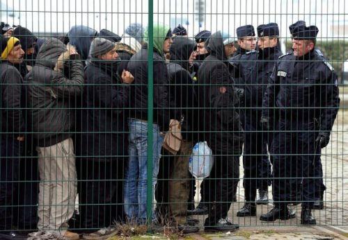 Des migrants attendent le 28 février 2013 à Calais sous l'oeil de la police un repas chaud de la Belle étoile. (Photo Philippe Huguen. AFP)