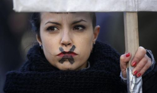 616417-a-woman-with-a-cross-painted-over-her-mouth-attends-a-protest-against-a-government-plan-to-limit-abo