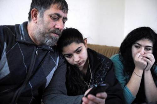 Leonarda Dibrabi entre son père Resat et sa soeur Ljaria, le 28 janvier 2014 à Mitrovica à l'annonce de la décision du tribunal administratif de Besançon