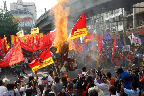 Protesters burn an effigy of President Benigno Aquino during a Labor Day protest outside the presidential palace in Manila