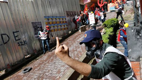 Protester gestures at riot police during a May Day demonstration in Istanbul