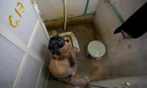 Un travailleur se lave avec de l'eau salée dans les toilettes. (Photo : Pete Pattisson)