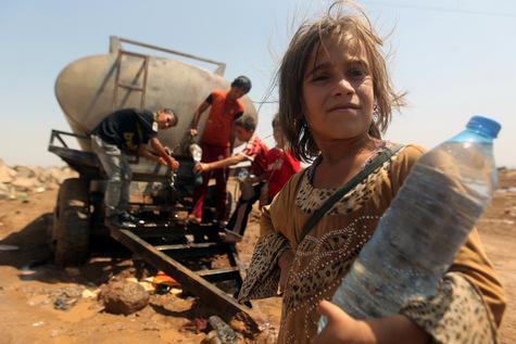 De jeunes réfugiés irakiens Yazidi remplissent des bouteilles d'eau au camp Newroz dans la province de Hasaka, au nord est de la Syrie, le 14 Août 2014.
