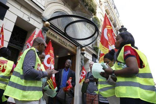 Des employés de l'hôtel Park Hyatt Vendôme à Paris, agitent des drapeaux de la CGT, le 19 septembre 2014 (Photo Thomas Samson. AFP)