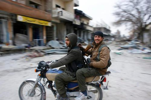 Fighters of the Kurdish People's Protection Units (YPG) patrol on a motorcycle in the streets of the northern Syrian town of Kobani