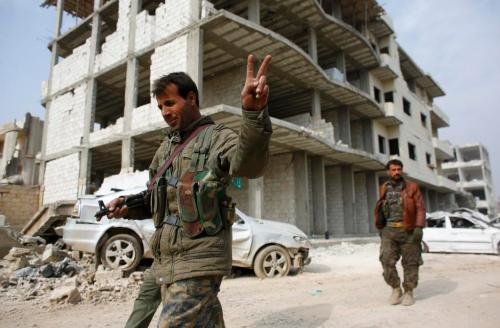 A fighter of the Kurdish People's Protection Units (YPG) flashes a V-sign as he patrols in the streets in the northern Syrian town of Kobani