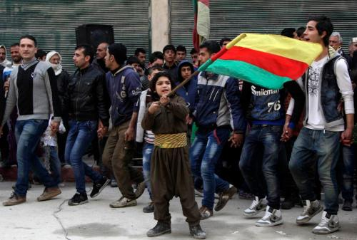 A Kurdish boy waves Kurdish flag during celebration after it was reported that Kurdish forces took control of Kobani, in Aleppo