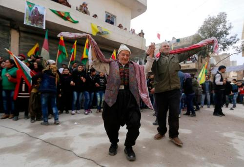 Kurdish civilians perform a traditional dance as they celebrate, after reports of Kurdish forces taking control of the Syrian town of Kobani, in Aleppo