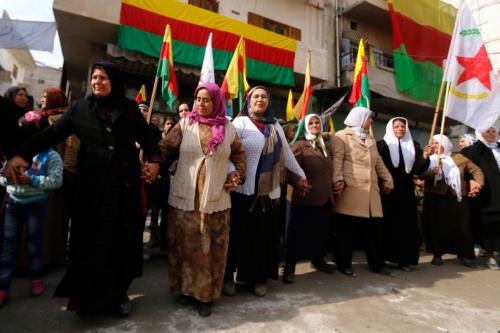 Kurdish women perform traditional dance as they celebrate, after reports of Kurdish forces taking control of Syrian town of Kobani, in Aleppo