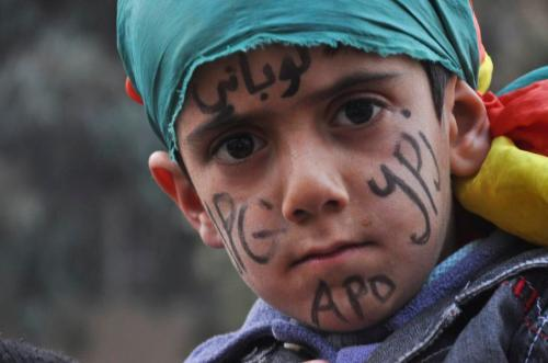 "A Kurdish boy with ""Kobani"" written on his forehead takes part in a celebration in the Syrian Kurdish city of Qamishli"