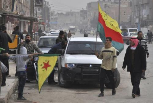 Kurdish civilians carry YPG flags as they walk along a street in the Syrian Kurdish city of Qamishli