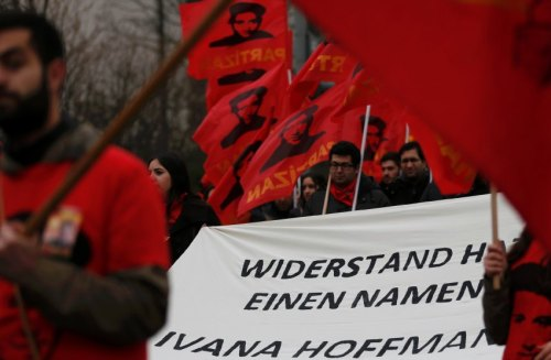People carry banners and flags with portraits of Ivana Hoffmann during a commemoration parade in Duisburg