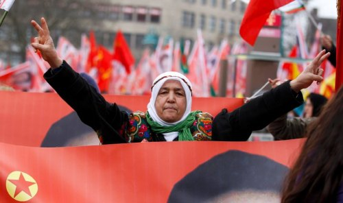 A woman flashes V-signs as she takes part in a commemoration parade in Duisburg