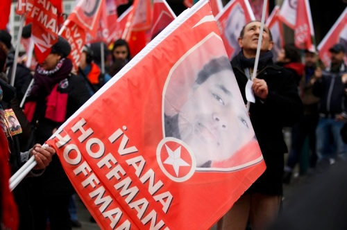 People carry flags with portraits of Hoffmann during a commemoration parade in Duisburg