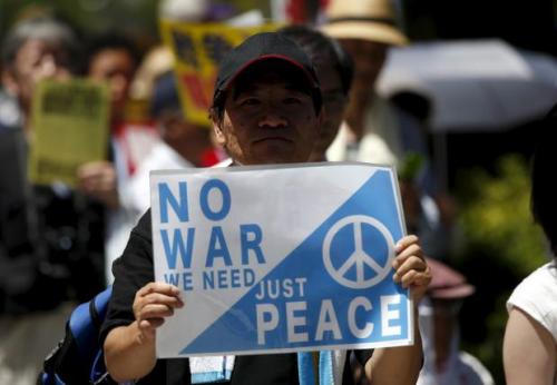 A protester holds a placard during a rally against Japan's Prime Minister Shinzo Abe's administration and his security-related legislation in front of the parliament building in Tokyo July 15, 2015.   REUTERS/Issei Kato