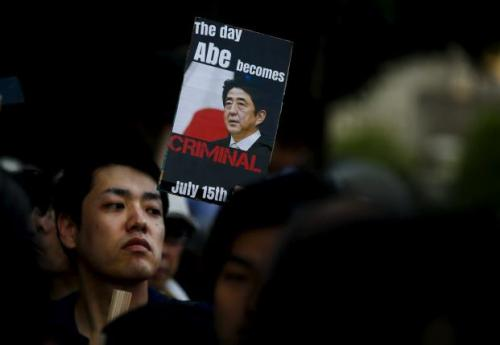 Man holds placard during anti-government rally in front of parliament in Tokyo