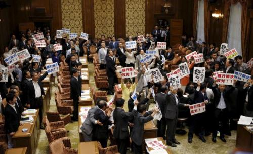 "Yasukazu Hamada (top, 2nd R), chairman of the Upper House Special Committee on Security, is surrounded by opposition lawmakers brandishing signs that read ""Abe politics is unforgivable"" and ""Against ramming bills through"" during a vote on security-related legislation at the parliament in Tokyo July 15, 2015. REUTERS/Toru Hanai"