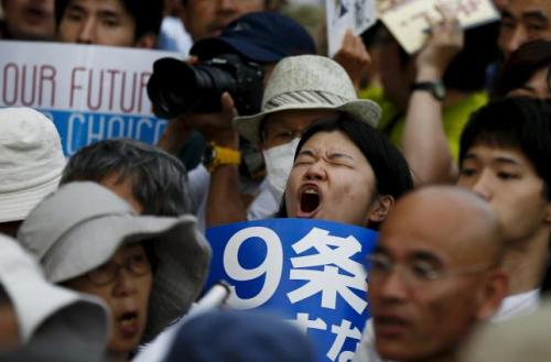 People shout slogans during a rally against Japan's Prime Minister Shinzo Abe's administration and his security-related legislation in front of the parliament building in Tokyo July 15, 2015.   REUTERS/Thomas Peter