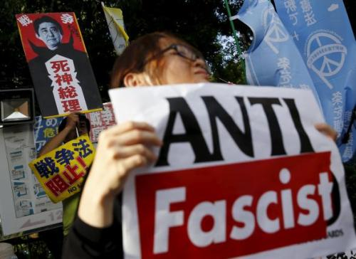 People hold placards during anti-government rally in front of parliament in Tokyo