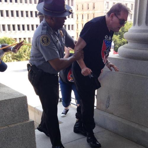 Ironie : c'est un un policier noir qui aide un raciste à sortir de la foule