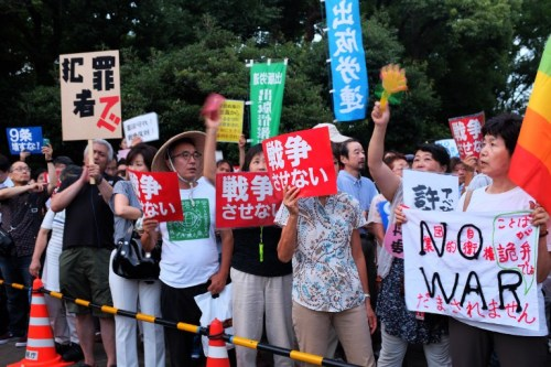 Civic group members stage an anti-government rally outside the National Diet in Tokyo on July 17, 2015. Controversial security bills that opponents say will undermine 70 years of pacifism and could see Japanese troops fighting abroad for the first time since World War II, passed through the powerful lower house of parliament July 16.     AFP PHOTO / KAZUHIRO NOGI