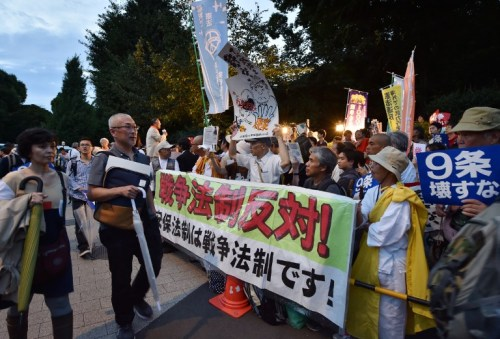Civic group members stage an anti-government rally outside the National Diet in Tokyo on July 17, 2015 to protest against the controversial security bills. Controversial security bills that opponents say will undermine 70 years of pacifism and could see Japanese troops fighting abroad for the first time since World War II, passed through the powerful lower house of parliament July 16.     AFP PHOTO / KAZUHIRO NOGI