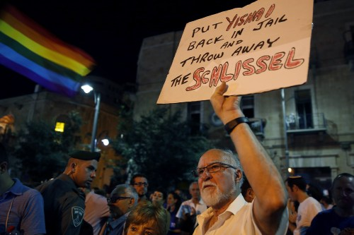 A man holds a placard as thousands of Israelis from the gay community and supporters gather in downtown Jerusalem on August 1, 2015 to protest against discrimination and violence against the gay community following an attack at the Jerusalem Gay Pride parade. An ultra-Orthodox Jew has been accused of stabbing six Gay Pride marchers in Jerusalem on July 30, gravely wounding one of them, just weeks after completing a 10-year sentence for a similar attack, police and medics said. AFP PHOTO / GALI TIBBON