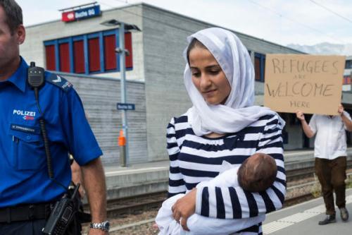 Eine Frau mit Kind auf dem Bahnhof Buchs SG. Im Hintergrund ein Plakat