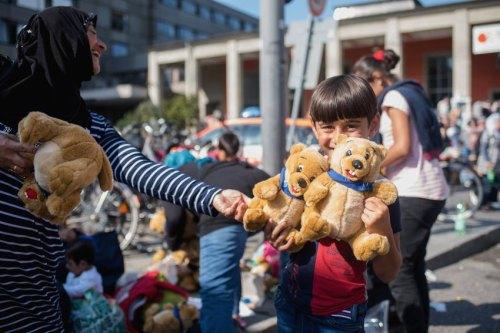 dpatopbilder Ein Flüchtlingskind freut sich am 01.09.2015 am Hauptbahnhof von München (Bayern) über geschenkte Stofftiere. Foto: Nicolas Armer/dpa +++(c) dpa - Bildfunk+++