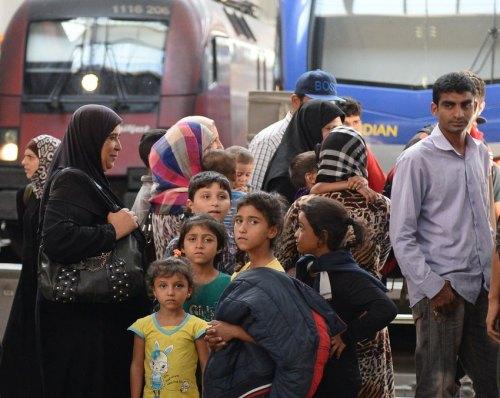 Eine Gruppe von Flüchtlingen aus Syrien steht am 31.08.2015 am Hauptbahnhof in München (Bayern) vor zwei Zügen. Etwa 50-60 Syrer kamen kurz zuvor mit einem Zug aus Ungarn in München an. Foto: Andreas Gebert/dpa +++(c) dpa - Bildfunk+++
