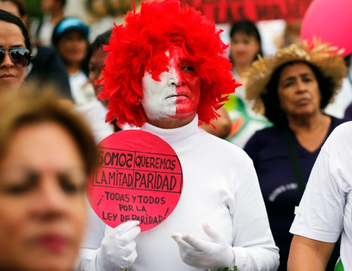 "A women holds a poster with a message that reads in Spanish, ""We are the other half, We want equality, all men , nd all women for the Law of Equality,"" in front of the National Congress building, during a protest demanding a law for equality in political representation, marking International Women's Day in Asuncion, Paraguay, Tuesday, March 8, 2016. (AP Photo/Jorge Saenz)"