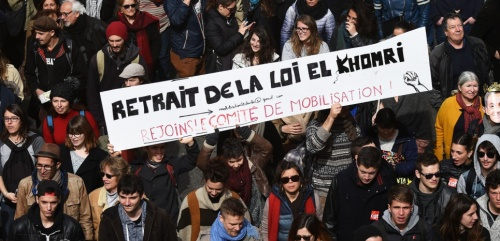 "People hold a cardboard reading ""Withdrawal of the El Khomri law - Join the mobilization committee"" as they take part in a nationwide day of protest against deeply unpopular labour reforms that have divided the Socialist government and raised hackles in a country accustomed to iron-clad job security, on March 9, 2016 in Marseille, southern France. France's government has faced massive blowback -- including from within its ranks -- to measures that would give bosses more flexibility in hiring and firing. / AFP / ANNE-CHRISTINE POUJOULAT"