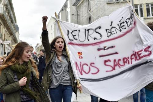 "A young woman holds up her fist as she chants slogans and holds a banner reading ""their gains = our sacrifices"" as thousands of people demonstrate on March 9, 2016 in Nantes, western France, as part a nationwide day of protest against proposed labour reforms. France faced a wave of protests against deeply unpopular labour reforms that have divided an already-fractured Socialist government and raised hackles in a country accustomed to iron-clad job security. / AFP / LOIC VENANCE"