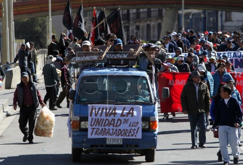 epa05286420 Bolivians participate in the International Workers Day parade in La Paz, Bolivia, 1 May 2016. Labour Day, or May Day, is observed all over the world on the first day of May to celebrate the economic and social achievements of workers and fight for labourers' rights. The sign on the van reads 'Long Live the Unity of the Workers'  EPA/MARTIN ALIPAZ