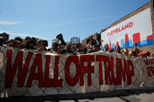 People stand behind a sign during protests against Republican U.S. presidential nominee Donald Trump outside the Republican National Convention in Cleveland, Ohio, U.S., July 20, 2016.  REUTERS/Andrew Kelly