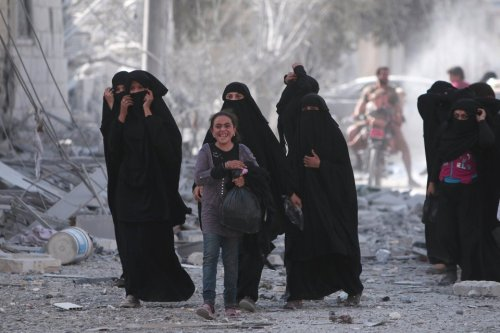 A girl reacts while walking with women after they were evacuated with others by the Syria Democratic Forces (SDF) fighters from an Islamic State-controlled neighbourhood of Manbij