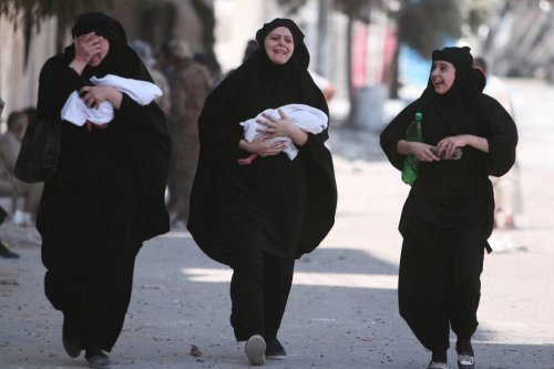 Women carry newborn babies while reacting after they were evacuated by the Syria Democratic Forces (SDF) fighters from an Islamic State-controlled neighbourhood of Manbij