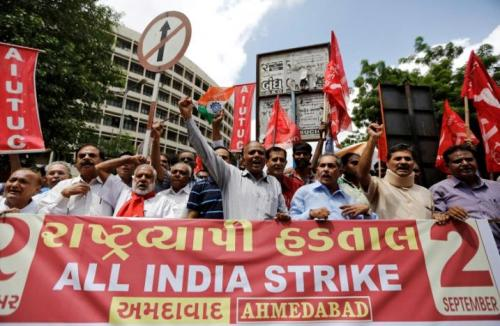 Workers from various trade unions shout slogans during a nationwide strike in Ahmedabad