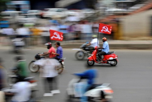 Workers from different trade unions ride motorcycles during a protest rally as part of a nationwide strike in Bengaluru