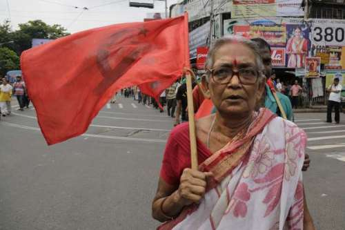 A supporter of the Communist Party of India-Marxist (CPIM) walks with the party flag as she joins with others during a nationwide strike in Kolkata, India, Friday, Sept. 2, 2016. The strike was called against allegedly government's anti labor policies and demanded higher minimum wages and provision of social security to unorganized workers. (AP Photo/Bikas Das)